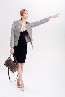 Woman catching taxi. young beautiful business woman blonde in black dress, jacket waving to stop a taxi on gray background