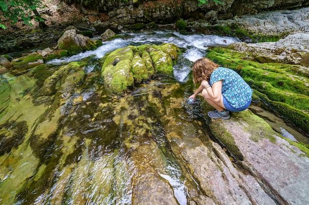 Женщина ловит воду из чистой реки в горах. красота и экология в месте без загрязнения.