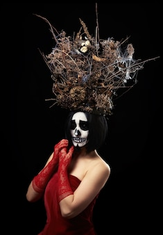 Woman of caucasian appearance with skeleton make-up stands in a red dress with a large crown of dry branches