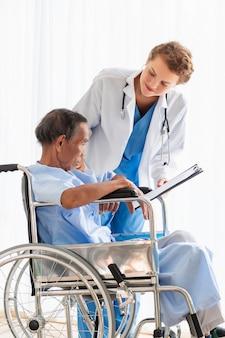 安心と病室で患者と議論する女性白人専門医師。