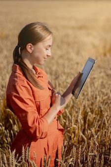 小麦の品質をチェックする分野の女性白人技術者農学者タブレットコンピューター