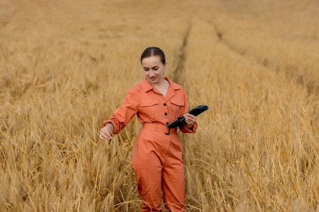Woman caucasian technologist agronomist with tablet computer in the field of wheat checking quality and growth of crops for agriculture. concept of wheat testing