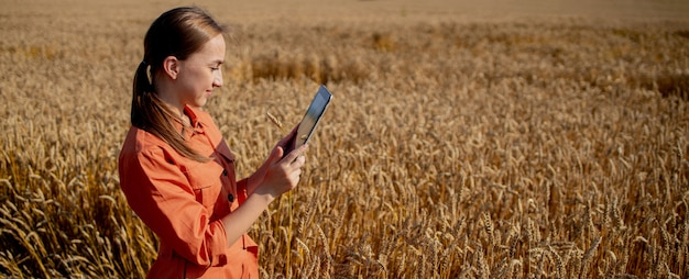 Woman caucasian technologist agronomist with tablet computer in the field of wheat checking quality