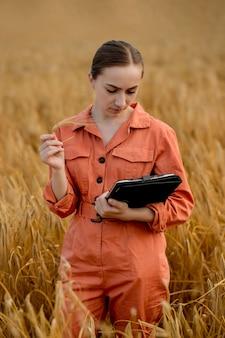 小麦の分野でタブレットコンピューターを使用して、農業用作物の品質と成長をチェックしている白人女性の技術者農学者。農業と収穫の概念。
