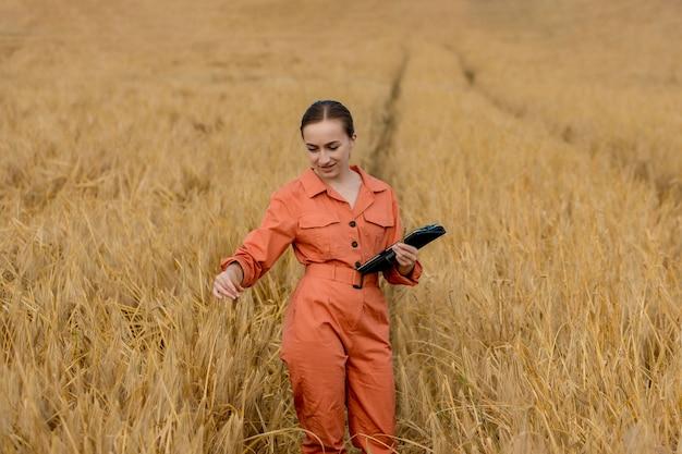 Кавказский технолог-агроном женщины с планшетным компьютером в области проверки качества и роста урожая пшеницы для сельского хозяйства. концепция тестирования пшеницы