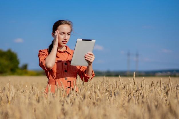 Кавказский технолог-агроном женщина с планшетным компьютером в области проверки качества пшеницы