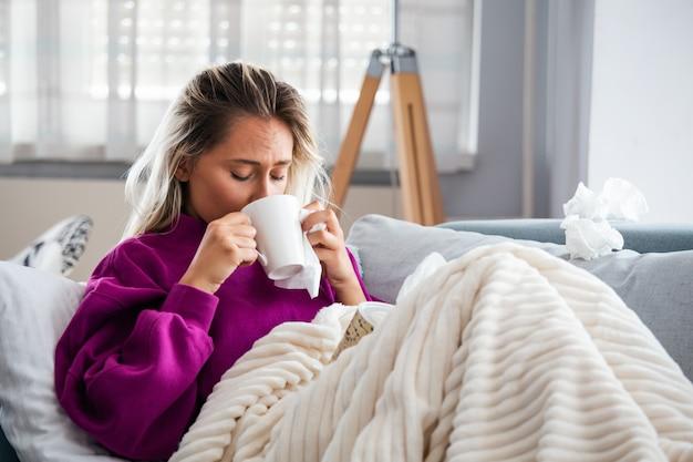 감기와 독감 조직으로 재채기를 잡은 여자.