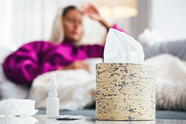 Woman caught cold and flu sneezing into tissue.