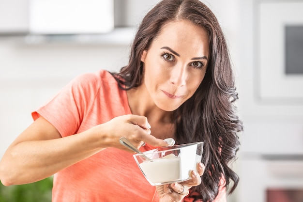 Woman caught tasting whipped cream from a bowl with her finger.