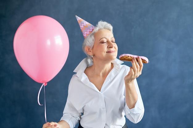 女性はペストリーを食べる風船で誕生日を祝う