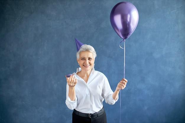 女性は風船で誕生日を祝う