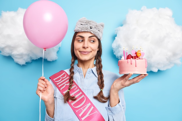 La donna festeggia il 26° compleanno in famiglia tiene la torta festosa gonfiato il palloncino di elio indossa la maglietta con il nastro si prepara per la festa isolata sul blu