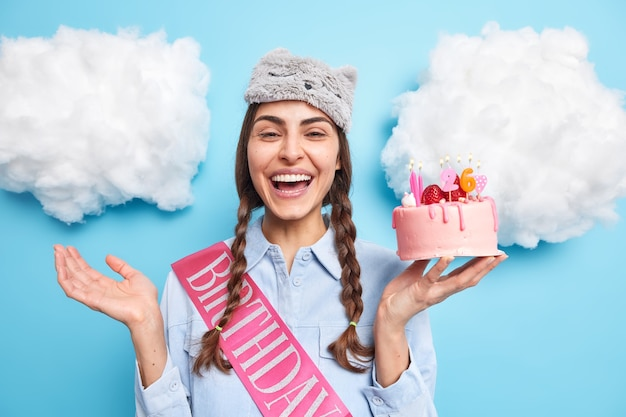 여자는 26 번째 생일을 축하하고 케이크를 입고 이마에 눈가리개를 두르고 친구의 축하를 받아 기쁘게 생각하는 두 개의 빗질 된 땋은 머리를 가지고 있습니다.
