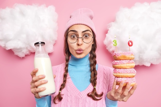 Женщина празднует 30-летие, держит глазированные вкусные пончики со свежим молоком, держит губы сложенными, носит повседневную одежду, изолированную на розовом