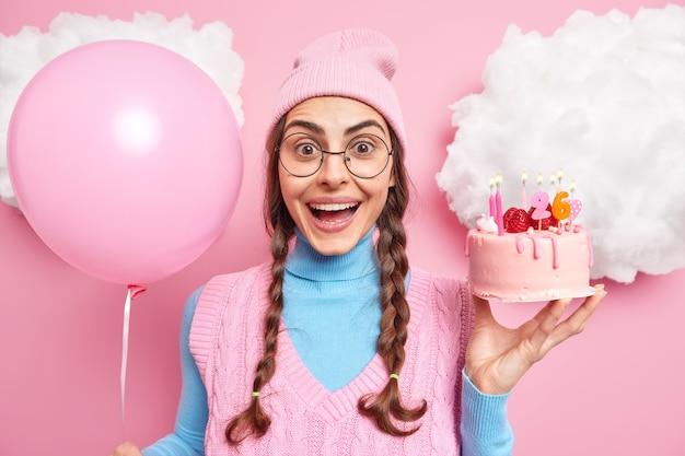 여자는 생일을 축하합니다 기쁜 친구들이 맛있는 케이크로 그녀의 포즈를 축하하기 위해 왔고 팽창 된 풍선은 분홍색에 대한 캐주얼 옷을 입습니다.