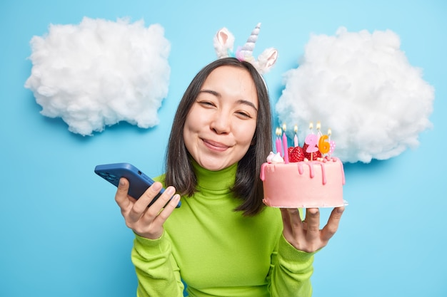 Woman celebrates birthday holds delicious strawberry cake and modern smartphone sends messages on inviations for party