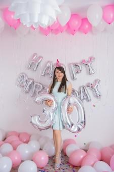 여자는 그녀의 30번째 생일을 축하합니다. 흰색과 분홍색 색 풍선과 흰색 벽 배경에서 파티를 위한 색종이 조각이 있는 생일 장식. 컨셉 풍선 30년. 실버 넘버 30