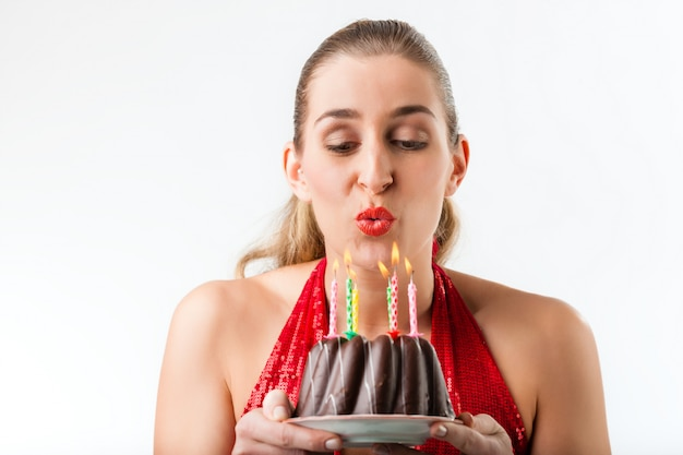 Woman celebrating birthday with cake and candles