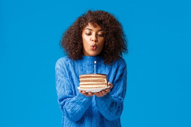 Woman celebrating her birthday on winter in family circle. cute and happy african-american girl