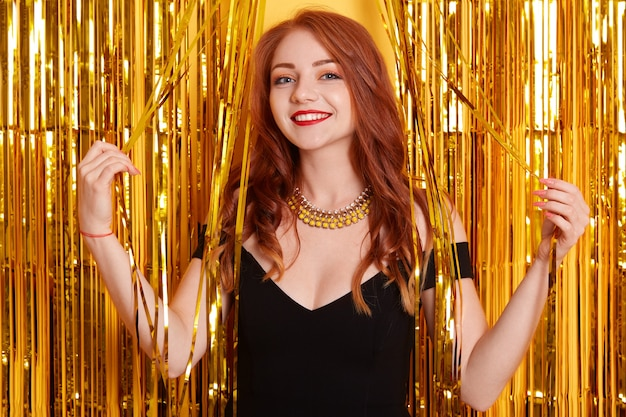 Woman celebrating new year party, beautiful smiling girl in black dress over golden tinsel on space,