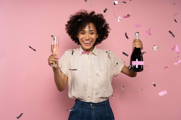 Женщина празднует с бокалом шампанского и бутылкой среди конфетти