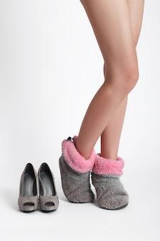 여자는 굽이 긴 불편한 신발을 부드럽고 편안한 슬리퍼로 바꿉니다. 퇴근 후 집에 있는 여자