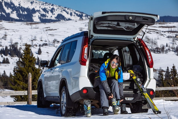 車のトランクに座ってスキーにブーツを変更する女性。晴れた日。冬のロードトリップ