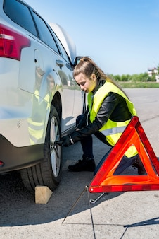 Woman changing damaged wheel of a car