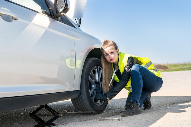 Woman changing damaged wheel and fixing it