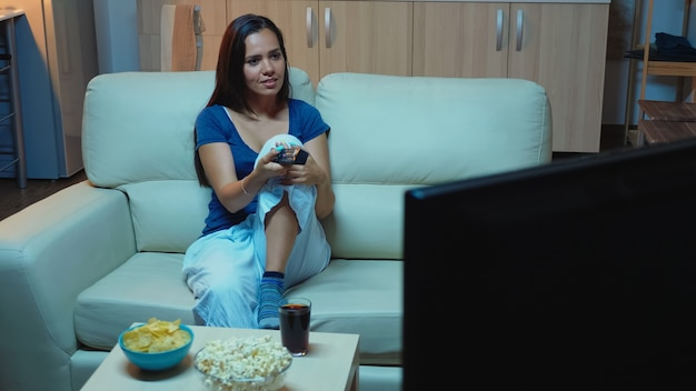 リモコンを使用してテレビチャンネルを変更する女性。退屈な、夜遅くに一人で家にいる女性は、コメディ映画を探しているリモコンを持って快適なソファに横になっているテレビを見てリラックスしています。 Premium写真