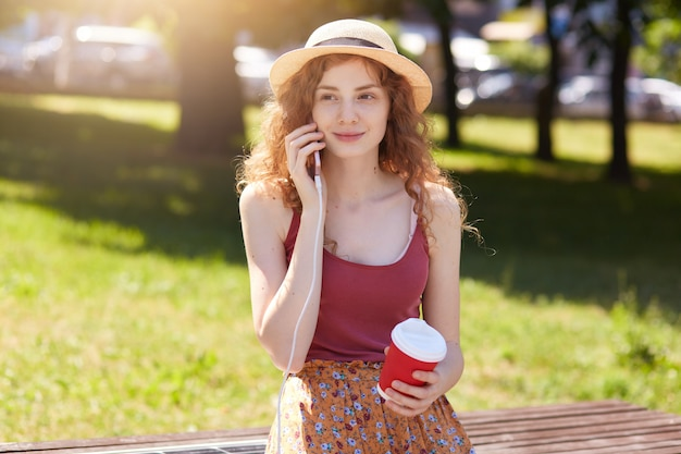 Woman charging cell phone via usb in public charging, charming female with foxy wavy hair sitting on bench with solar panel on street