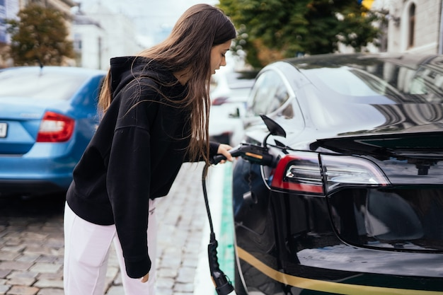 충전소에서 전기 자동차를 충전하는 여자.