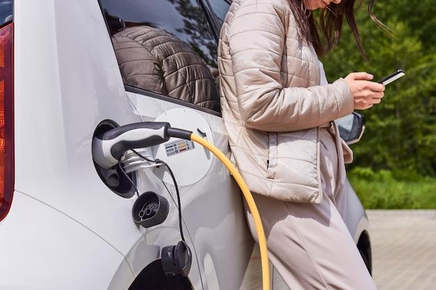 Женщина заряжает электромобиль