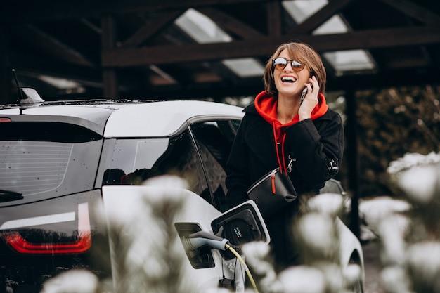 Женщина заряжает электро автомобиль и разговаривает по телефону