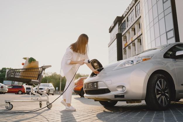 Женщина заряжает электро автомобиль на заправке