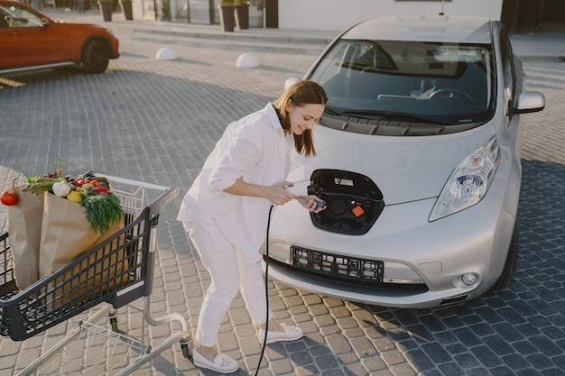 電気ガソリンスタンドで電気自動車を充電する女性
