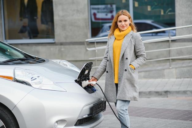전기 주유소에서 전기 자동차를 충전하는 여자