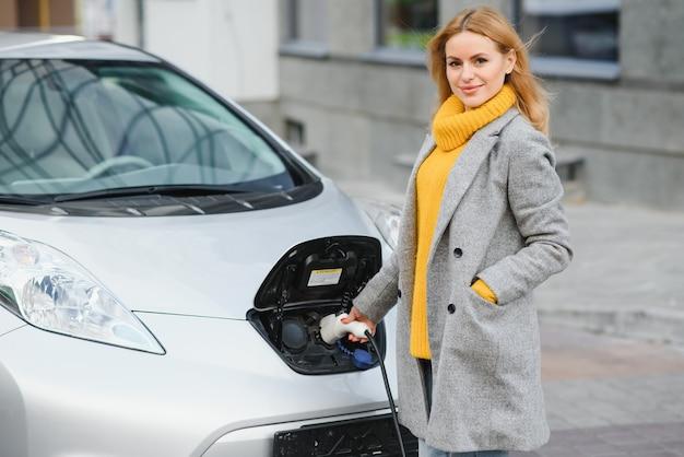 Женщина заряжает электроавтомобиль на азс