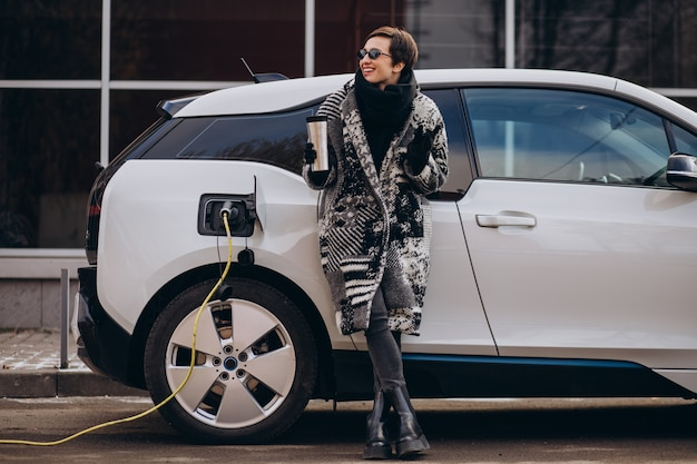거리에서 전기 자동차를 충전하는 여자