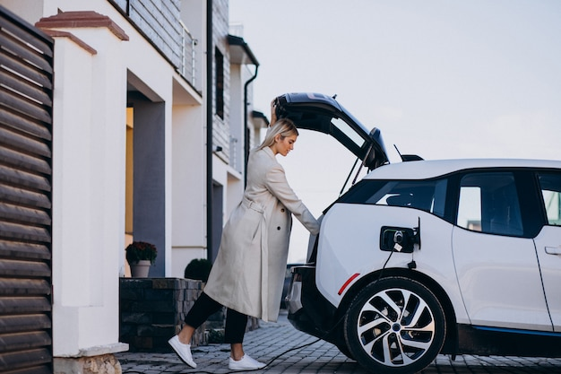 Woman charging electro car by her house
