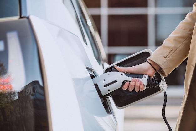 Donna che carica l'auto elettrica alla stazione di gas elettrica