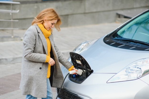 Woman charging electro car at the electric gas station