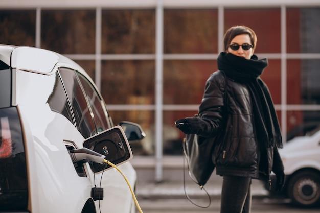 Donna che carica elettro automobile in strada