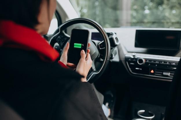 女性は彼女の車を充電し、彼女の電話でchergerを見て
