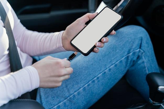 차에서 그녀의 전화를 충전하는 여자