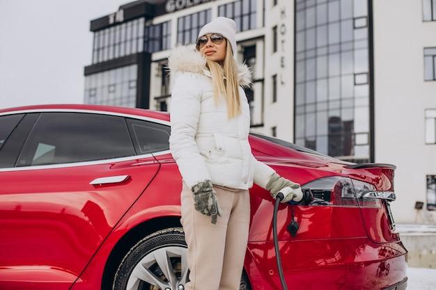 Женщина заряжает красный электромобиль, в зимнее время