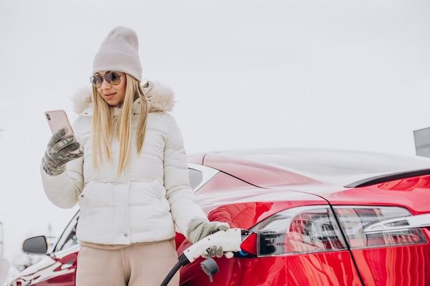 겨울철에 빨간 전기 자동차를 충전하는 여자