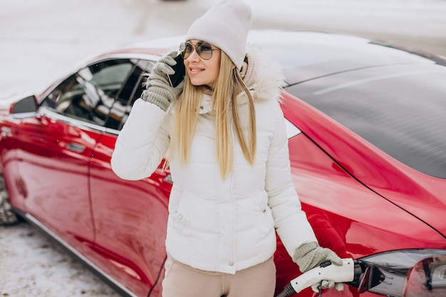Woman charging red electro car, in winter time