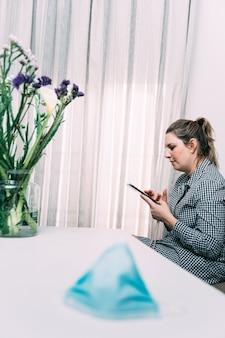 テーブルの上のフェイスマスクと彼女のスマートフォンでチャットする女性