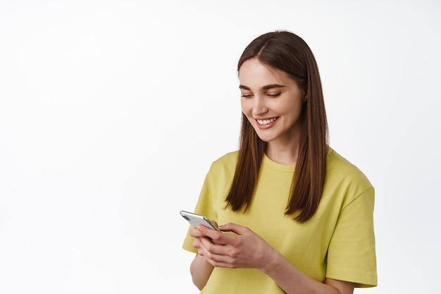 女性のチャット、電話でのテキストメッセージ、スマートフォンアプリの使用、画面の読み取りと笑顔、白の上に立つ